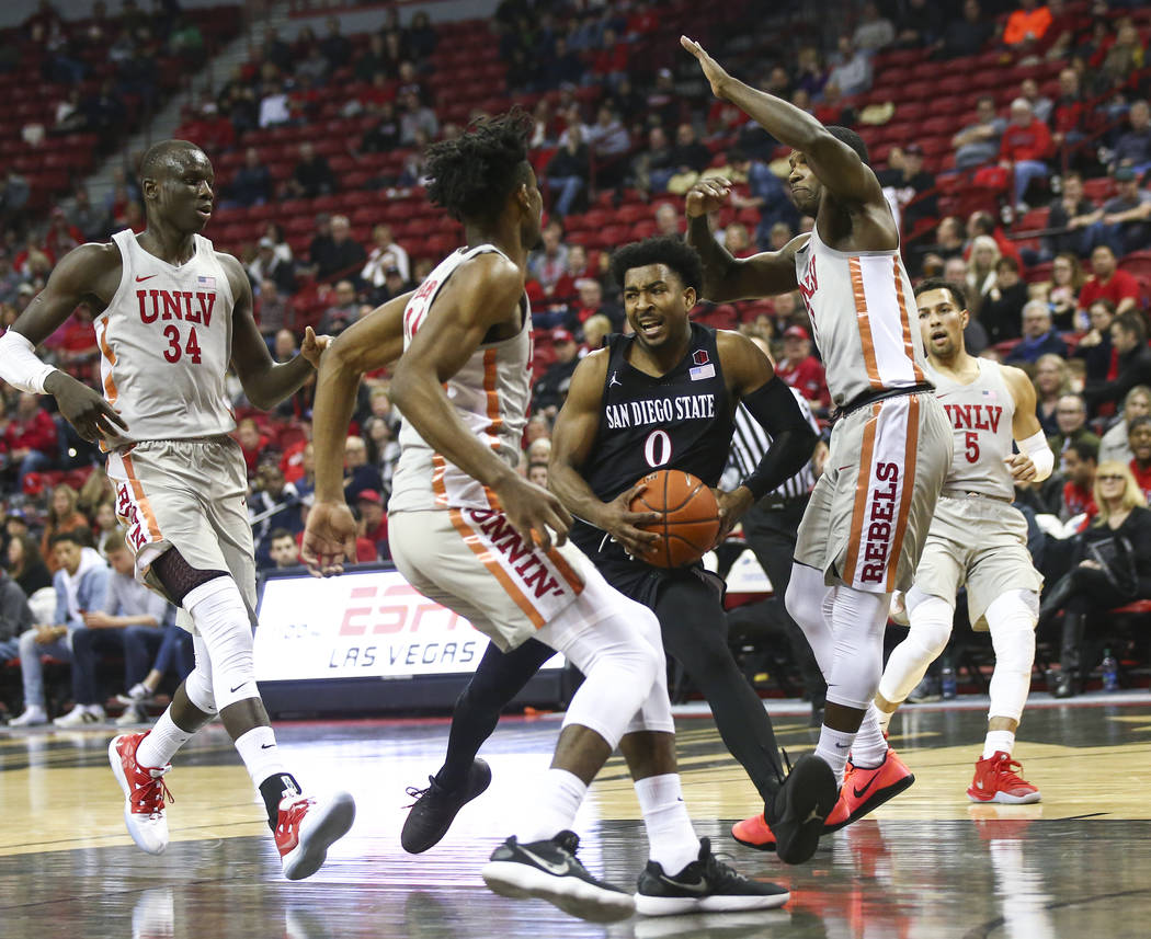 UNLV Rebels forward Joel Ntambwe, center left, and guard Amauri Hardy (3) defend as San Diego State Aztecs guard Devin Watson (0) tries to drives to the basket while UNLV Rebels forward Cheikh Mba ...