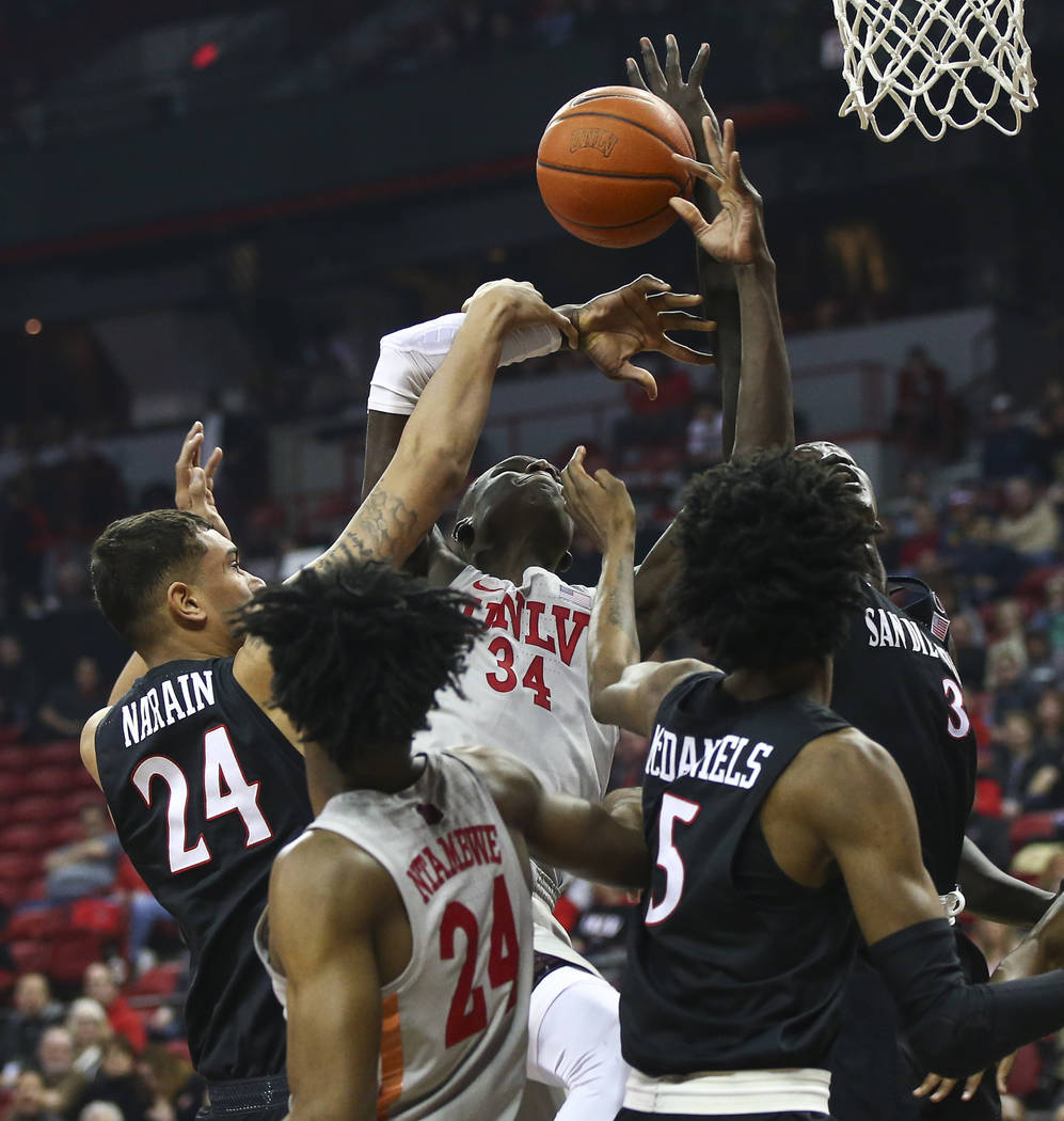 UNLV Rebels forward Cheikh Mbacke Diong (34) battles for a rebound against San Diego State Aztecs forwards Nolan Narain (24) and forward Aguek Arop (3) during the first half of a basketball game a ...
