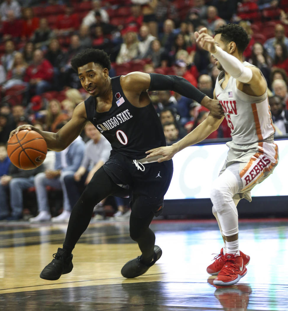 San Diego State Aztecs guard Devin Watson (0) drives the ball around UNLV Rebels guard Noah Robotham (5) during the first half of a basketball game at the Thomas & Mack Center in Las Vegas on ...