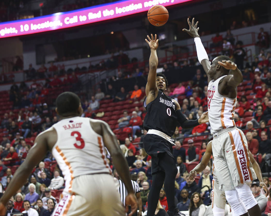 San Diego State Aztecs guard Devin Watson (0) shoots over UNLV Rebels forward Cheikh Mbacke Diong (34) during the first half of a basketball game at the Thomas & Mack Center in Las Vegas on Sa ...
