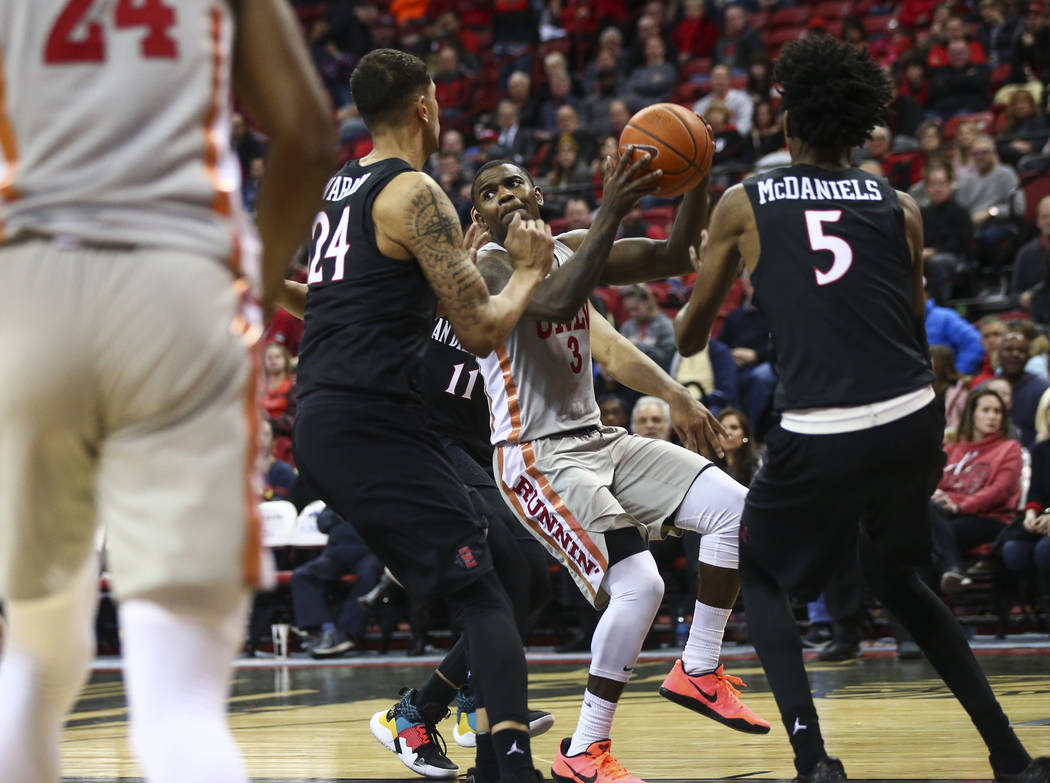 UNLV Rebels guard Amauri Hardy (3) moves the ball under pressure from San Diego State Aztecs forwards Nolan Narain (24) and Jalen McDaniels (5) during the second half of a basketball game at the T ...