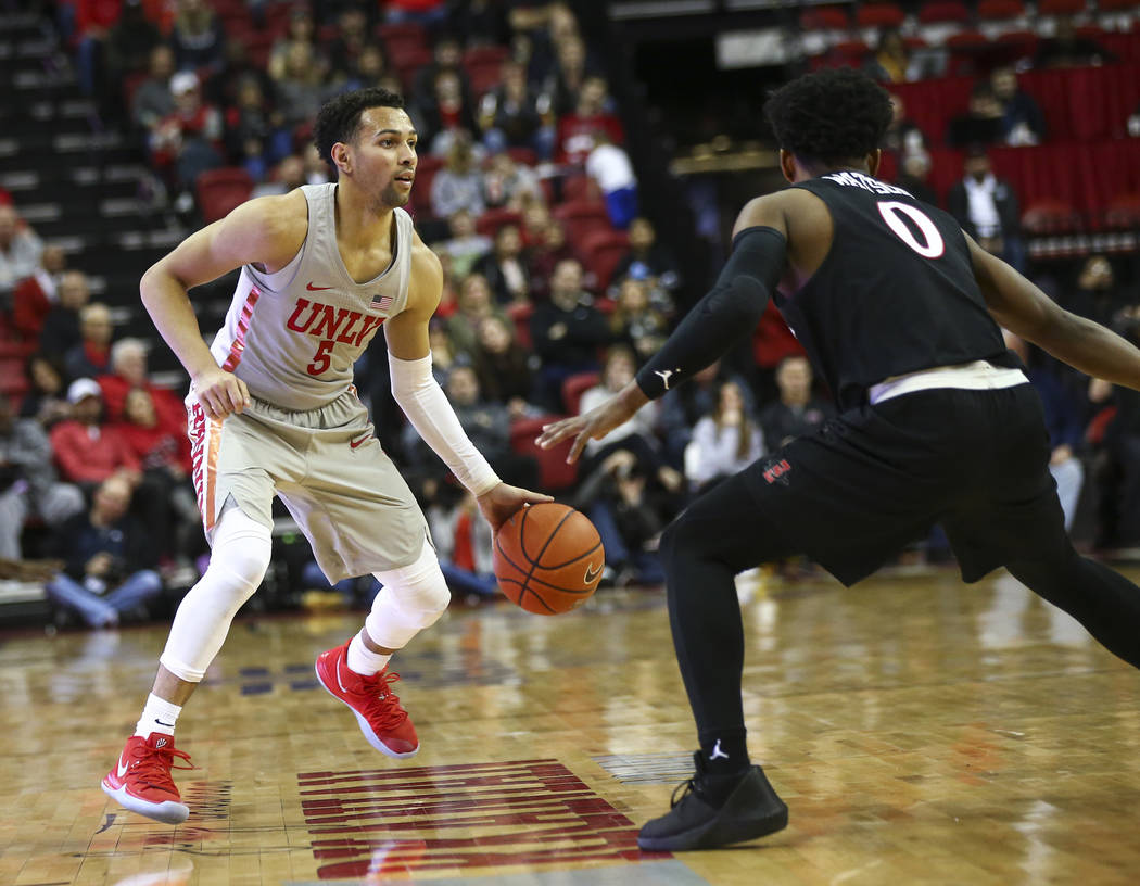 UNLV Rebels guard Noah Robotham (5) drives the ball around San Diego State Aztecs guard Devin Watson (0) during the second half of a basketball game at the Thomas & Mack Center in Las Vegas on ...