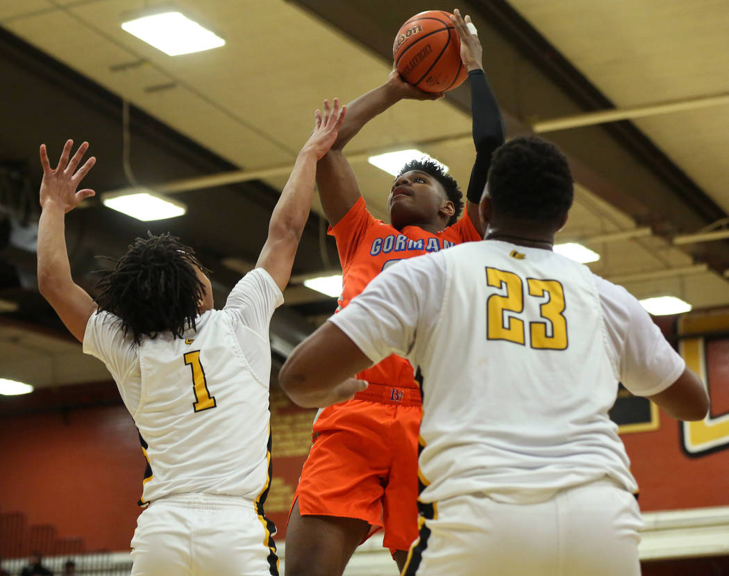 Bishop Gorman's Mwani Wilkinson (23) jumps up to take a shot while being guarded by Clark's Frankie Collins (1), left, and Antwon Jackson (23) during a basketball game at Clark High School in Las ...
