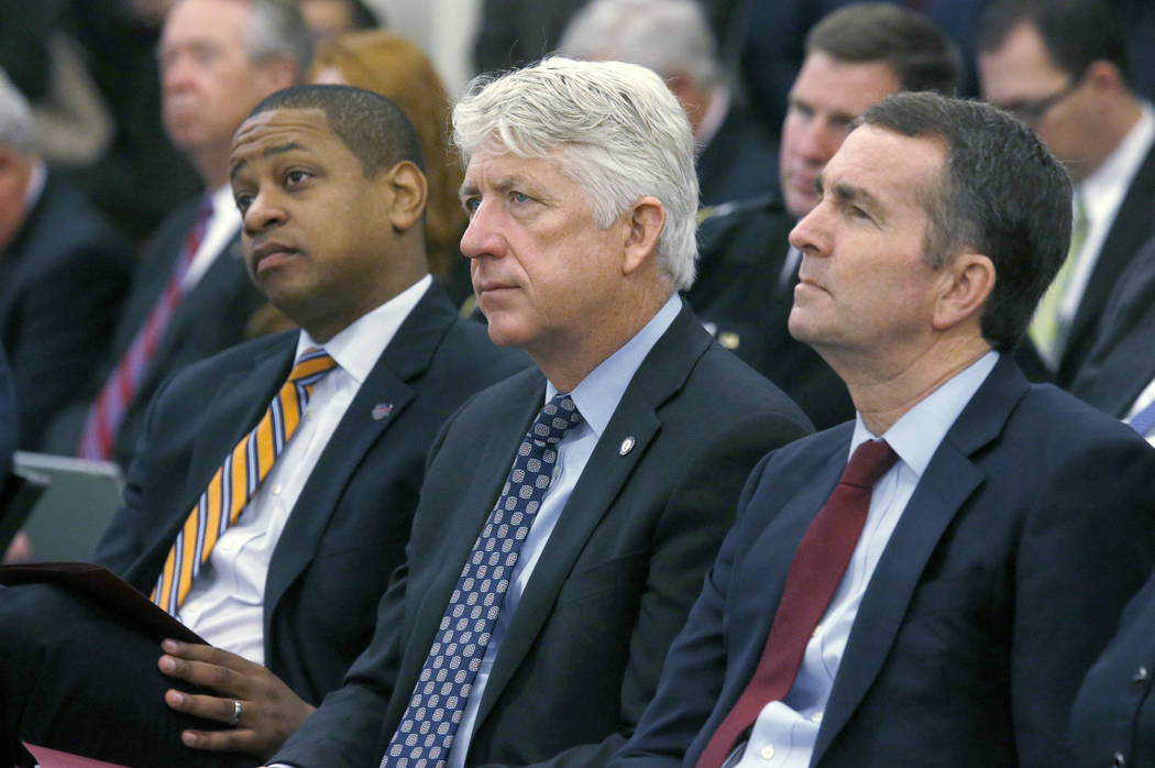 FILE - In this Dec. 18, 2017 file photo, from left, Lt. Governor-elect Justin Fairfax, Attorney General-elect Mark Herring and Governor-elect Ralph Northam listen as Virginia Governor Terry McAuli ...
