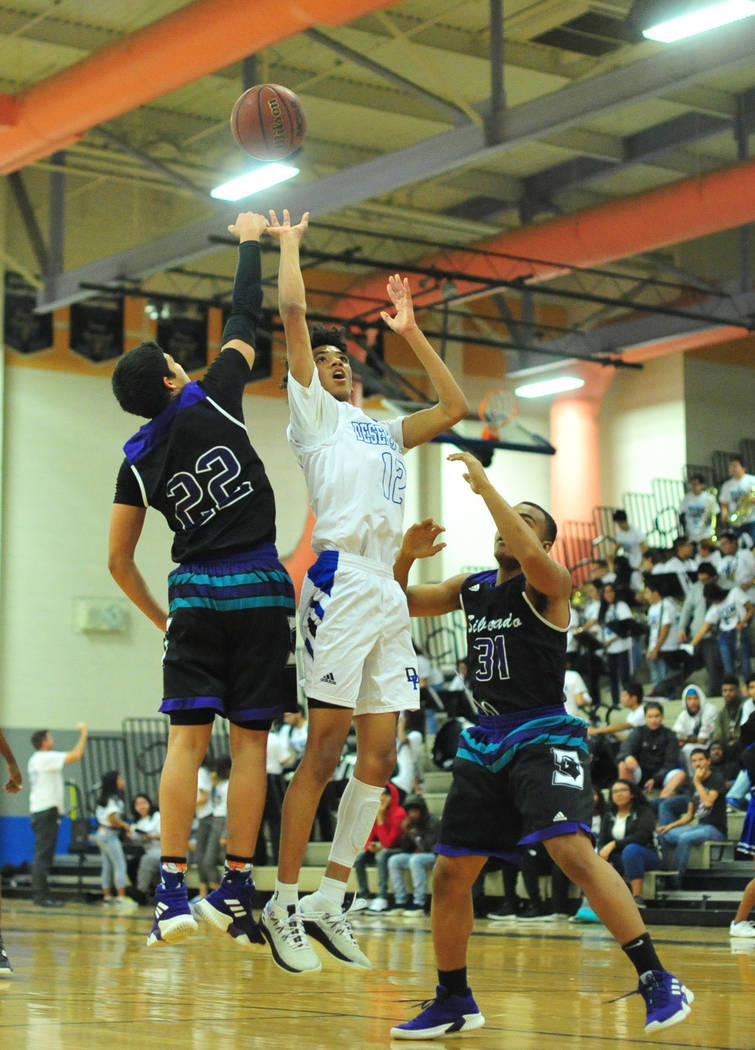 Desert Pines' Milos Uzan (12) takes a shot over Silverado's Noah Sherrard (22) and Terrel Williams (31) during the Desert Pines vs. Silverado High School basketball game at Desert Pines High Schoo ...