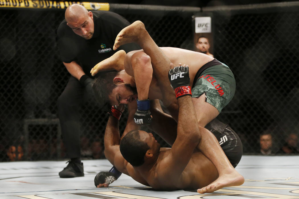 Kelvin Gastelum, top, from the United States, fights Ronaldo Souza, from Brazil, during their UFC middleweight mixed martial arts bout in Rio de Janeiro, Brazil, early Sunday, May 13, 2018. (AP Ph ...