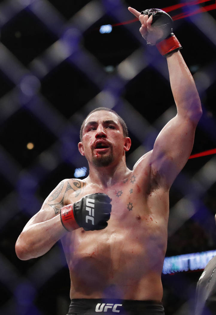 Robert Whittaker reacts after his middleweight title mixed martial arts bout against Yoel Romero at UFC 225, early Sunday, June 10, 2018, in Chicago. (AP Photo/Jim Young)