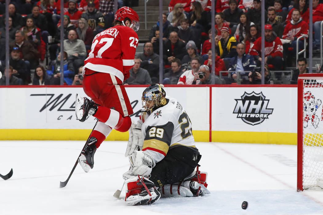Vegas Golden Knights goaltender Marc-Andre Fleury (29) blocks a shot as Detroit Red Wings center Michael Rasmussen (27) jumps out of the way in the second period of an NHL hockey game Thursday, Fe ...
