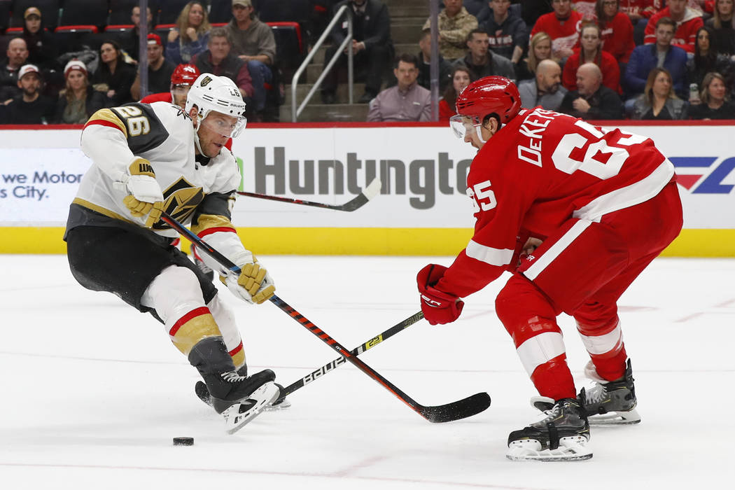 Detroit Red Wings defenseman Danny DeKeyser (65) pokes the puck away from Vegas Golden Knights center Paul Stastny (26) in the third period of an NHL hockey game Thursday, Feb. 7, 2019, in Detroit ...