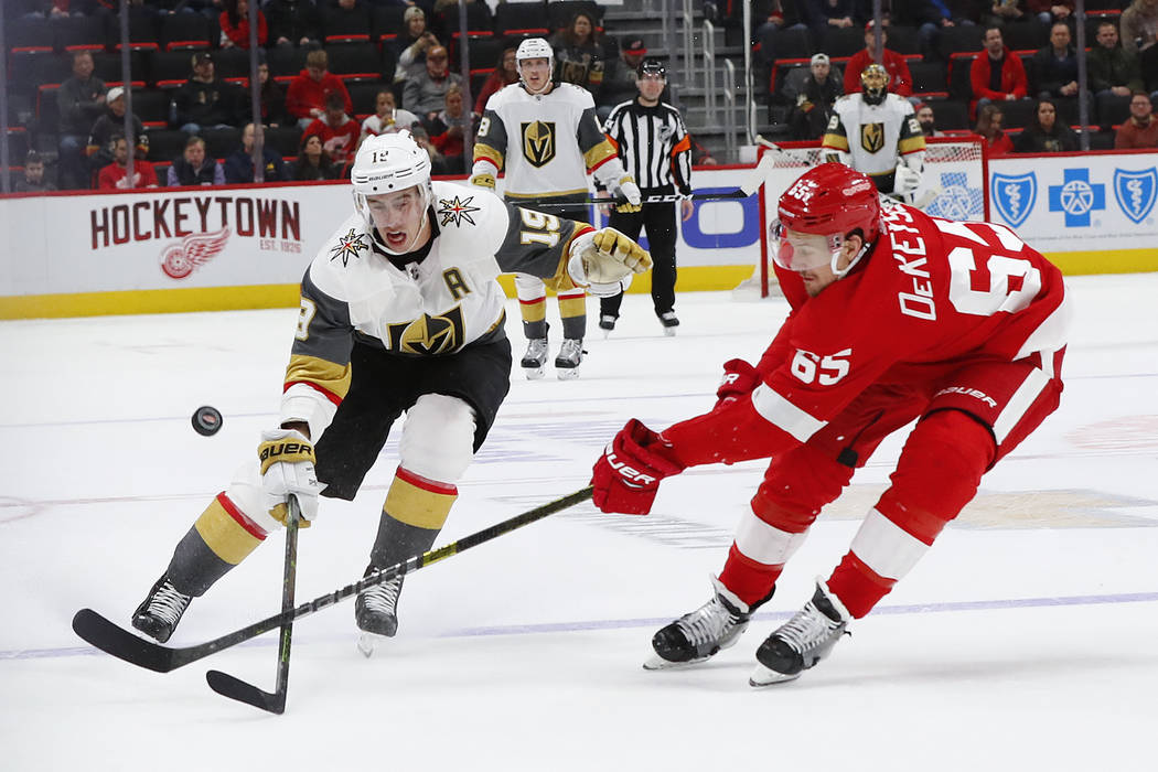 Detroit Red Wings defenseman Danny DeKeyser (65) knocks the puck away from Vegas Golden Knights right wing Reilly Smith (19) in the third period of an NHL hockey game Thursday, Feb. 7, 2019, in De ...