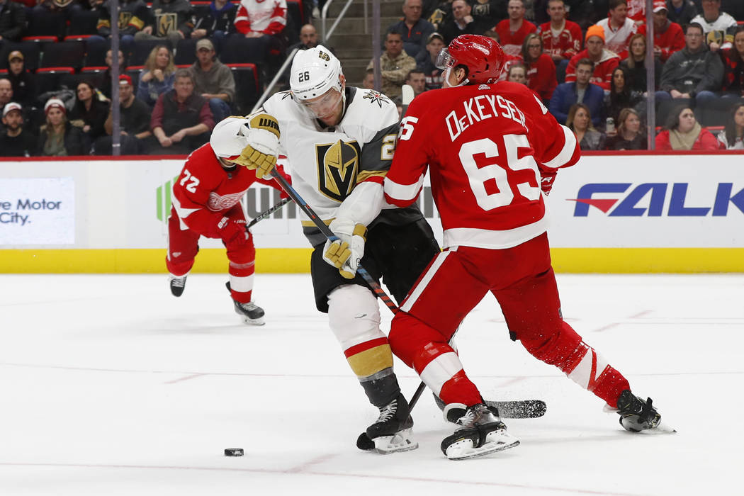 Detroit Red Wings defenseman Danny DeKeyser (65) takes Vegas Golden Knights center Paul Stastny (26) off the puck in the third period of an NHL hockey game Thursday, Feb. 7, 2019, in Detroit. (AP ...