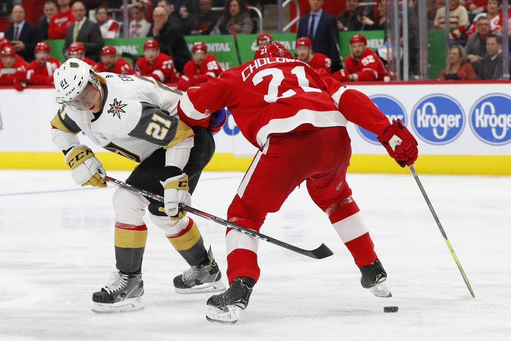 Vegas Golden Knights center Cody Eakin, left, shoots past Detroit Red Wings defenseman Dennis Cholowski (21) in the third period of an NHL hockey game Thursday, Feb. 7, 2019, in Detroit. (AP Photo ...
