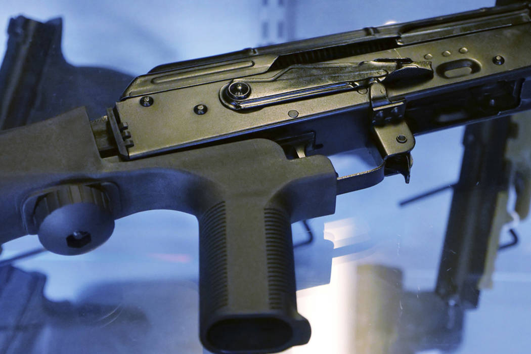 "A device called a ""bump stock"" is attached to a semi-automatic rifle at the Gun Vault store and shooting range in South Jordan, Utah on Oct. 4, 2017. (AP Photo/Rick Bowmer)"