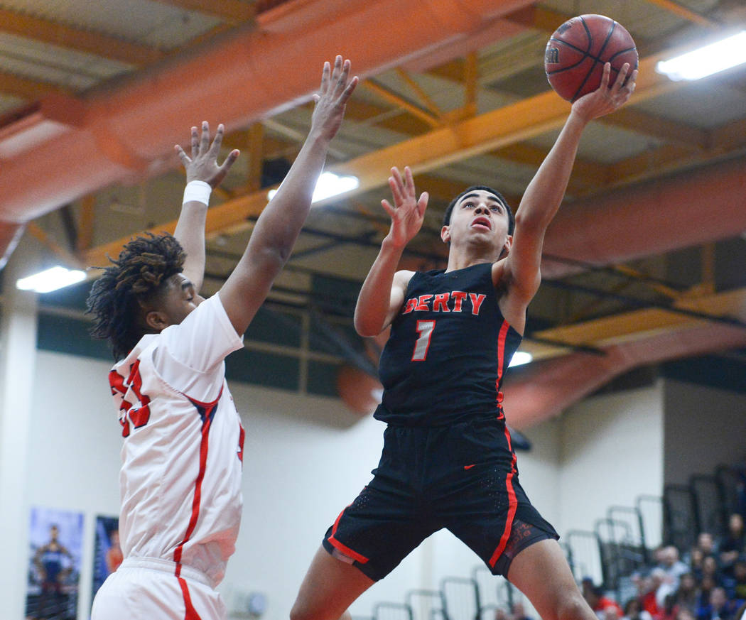 Liberty's Kobe Stroughter (1) shoots a lay up over Coronado's Jhaylon Martinez (33) in the first quarter of a game between Coronado High School and Liberty High School at Coronado High School in H ...