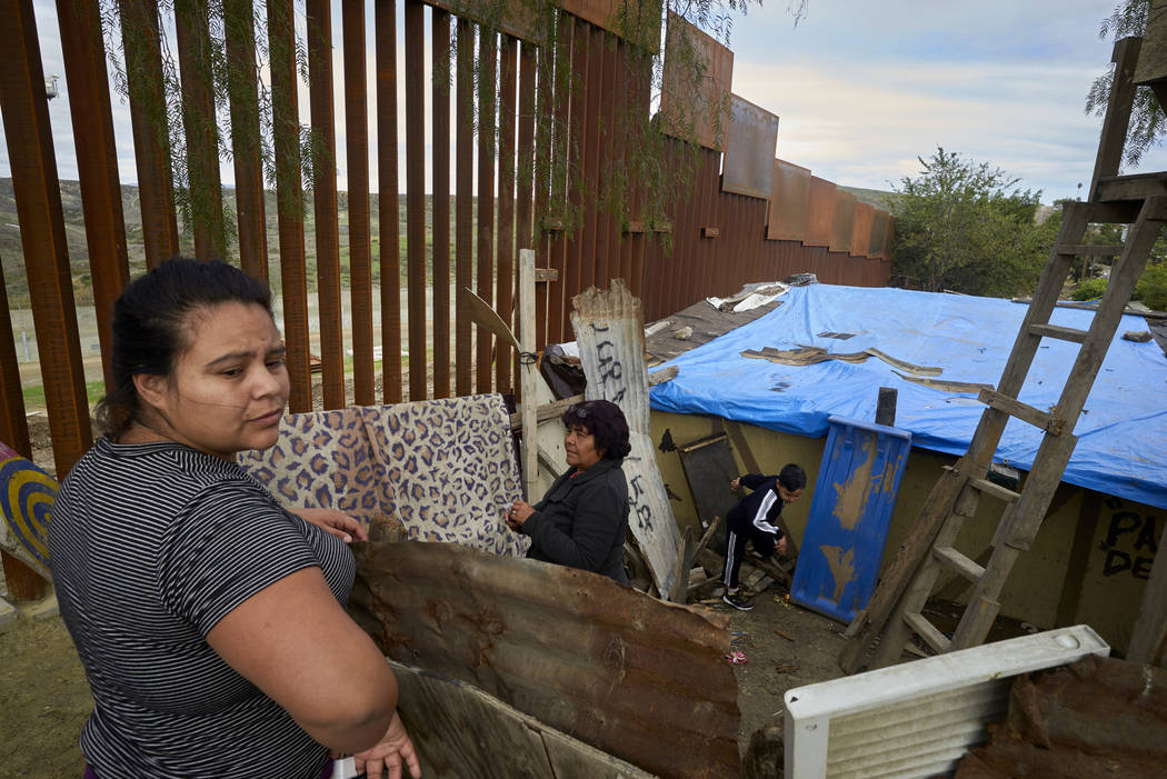 Yuli Arias, left, stands near a newly replaced section of the border wall as her mother, Esther Arias, center, stands in the family's house that was once threatened by construction along the borde ...