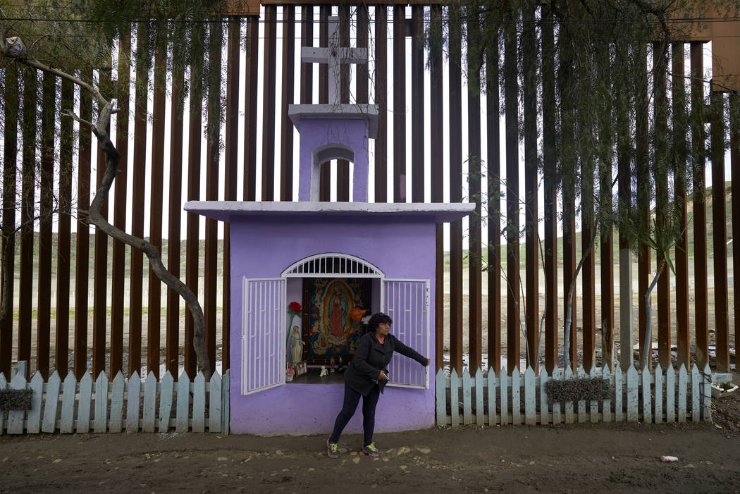Esther Arias opens a window on a shrine built by her father, Jose Arias, as a newly-replaced section of border wall sits behind, in Tijuana, Mexico, on Jan. 16, 2019. (AP Photo/Gregory Bull)