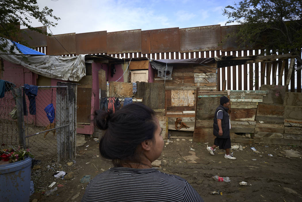 Yuli Arias, center, looks toward her home that was once threatened by construction of the newly replaced border wall, in her neighborhood in Tijuana, Mexico, as her nephew Rafael Arias passes, rig ...