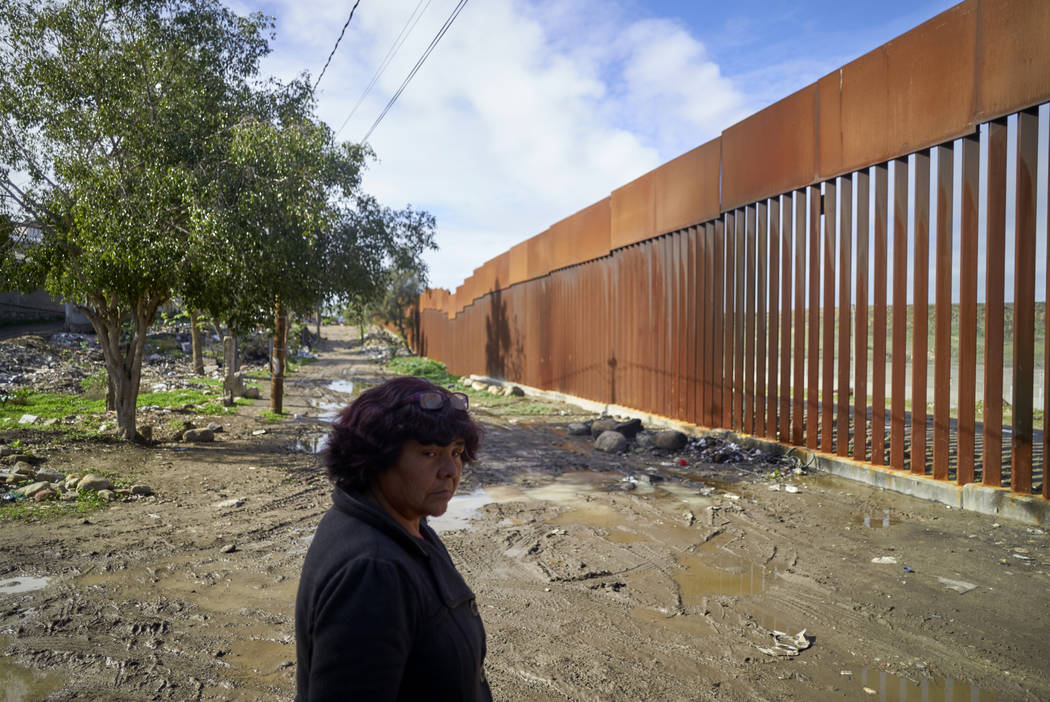 Esther Arias looks out towards a newly replaced section of border wall as she stands in her neighborhood in Tijuana, Mexico, in January 2019. (AP Photo/Gregory Bull)