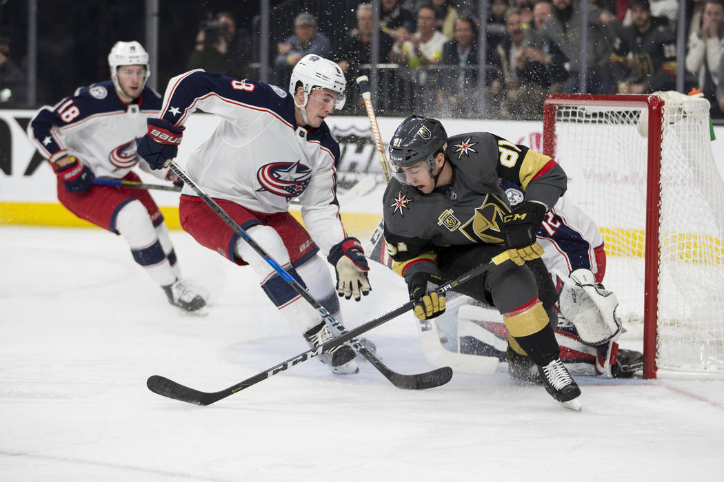 Vegas Golden Knights center Jonathan Marchessault (81) and Columbus Blue Jackets defenseman Zach Werenski (8) fight for possession in the NHL game at T-Mobile Arena Las Vegas, Tuesday, Jan. 23, 20 ...