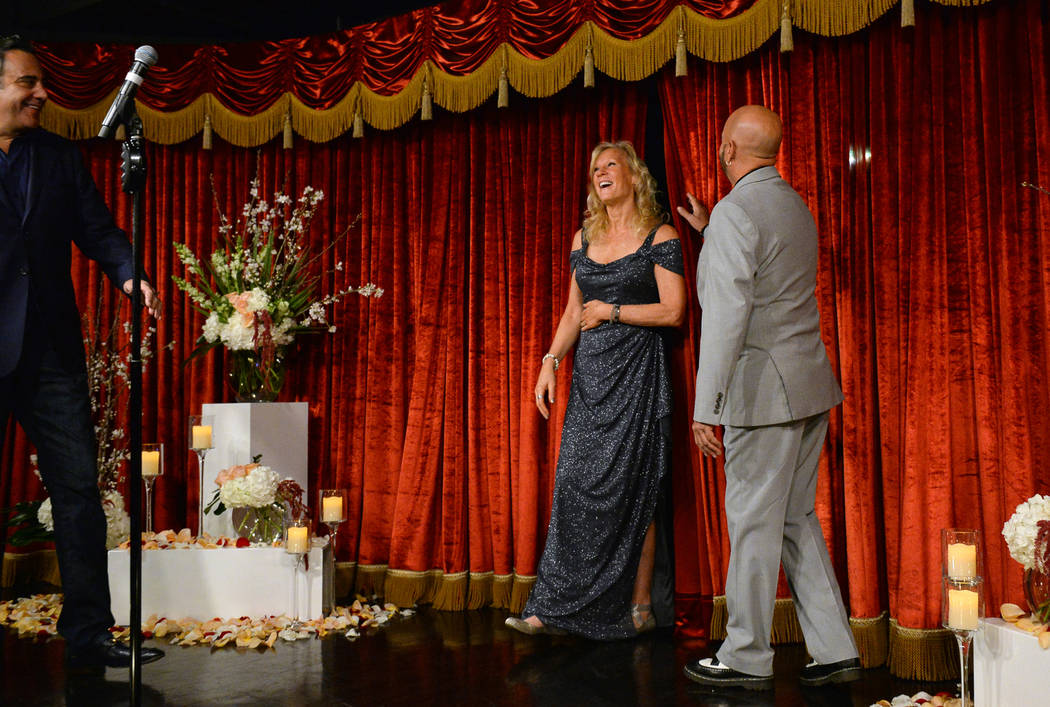 Cyndi Nelson walks out on stage as she is greeted by comedian Brad Garrett, left, and soon-to-be husband Rob Sherwood during their wedding ceremony at Brad Garrett's Comedy Club in the MGM Grand h ...