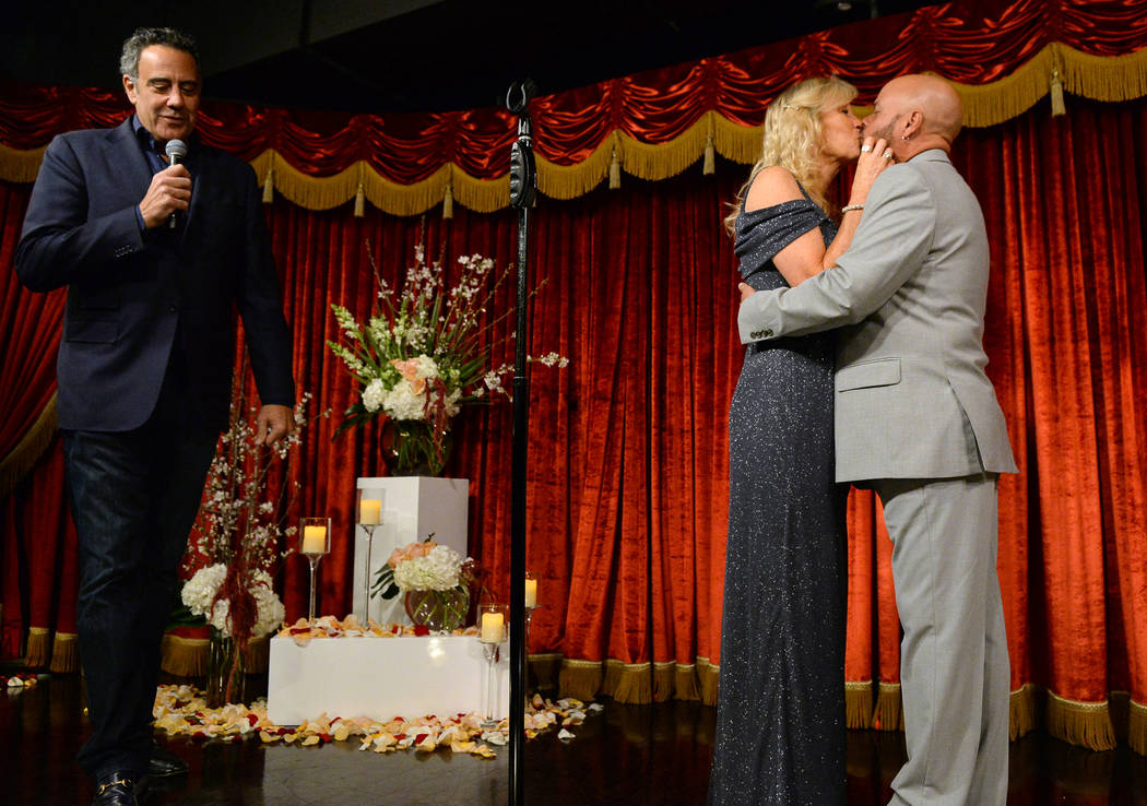 Comedian Brad Garrett, left, walks off as Cyndi Nelson and comedian Rob Sherwood kiss after stating their wedding vows at Brad Garrett's Comedy Club in the MGM Grand hotel-casino in Las Vegas, Sat ...