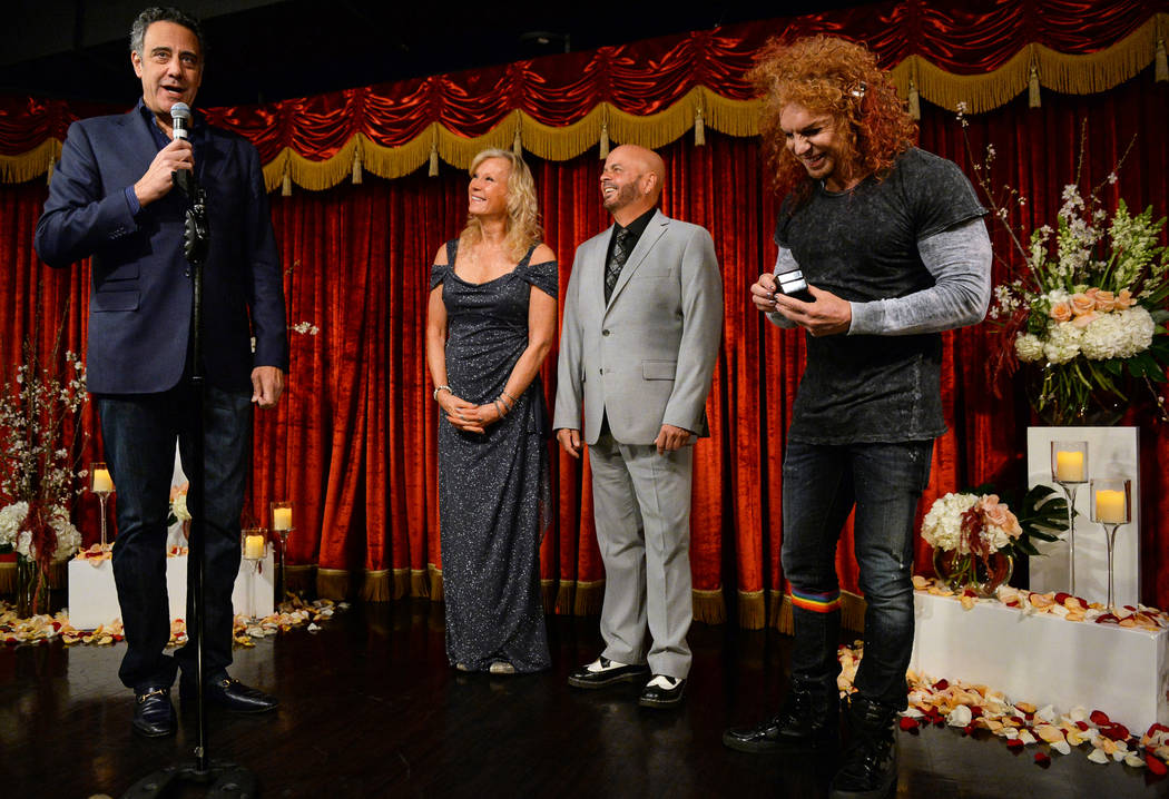 Comedian Brad Garrett, left, officiates the wedding of Cyndi Nelson and comedian Rob Sherwood as Scott Thompson, known professionally as Carrot Top, right, gets ready to present the wedding rings ...