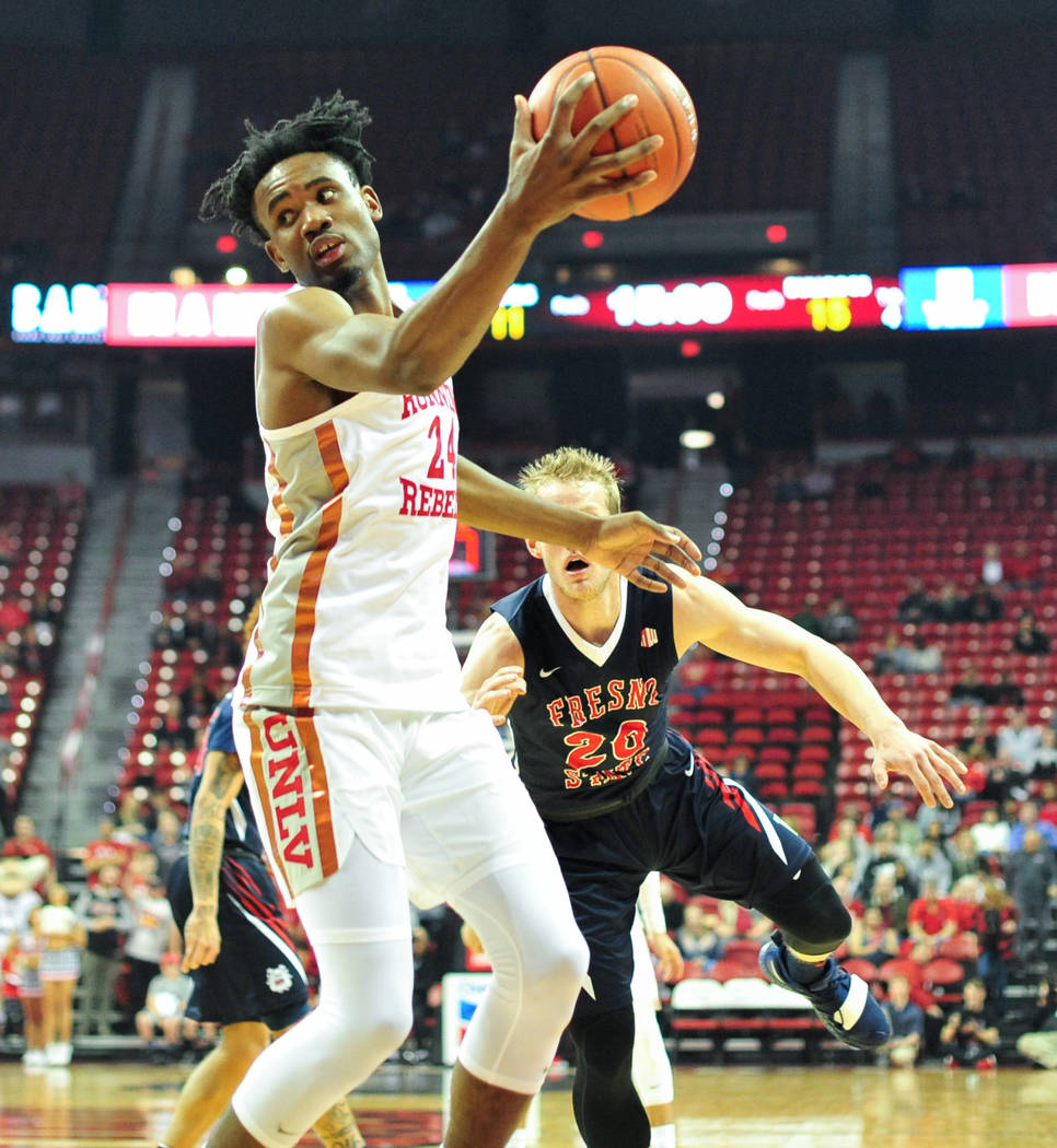 UNLV Rebels forward Joel Ntambwe (24) catches a pass with one hand while being guarded by Fresno State Bulldogs forward Sam Bittner (20) during the first half of a game between UNLV and Fresno Sta ...