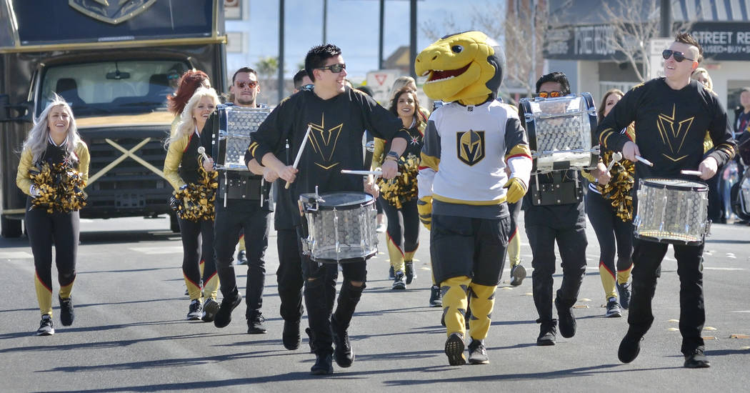 Members of the Golden Knights cheerleaders and Knight Line drum team march in a parade which was part of Chinese New Year celebrations on Fremont Street in Las Vegas on Saturday, Feb. 9, 2019. (Bi ...