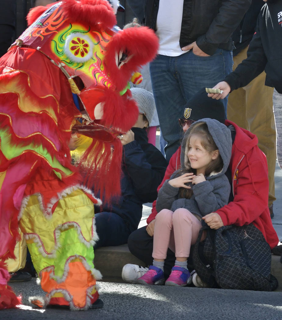 Ariel Dehner, 5, and her aunt Jenelle Lea watch as students from the Lohan School of Shaolin Kung Fu performing as dragons pass by during a parade which was part of Chinese New Year celebrations o ...