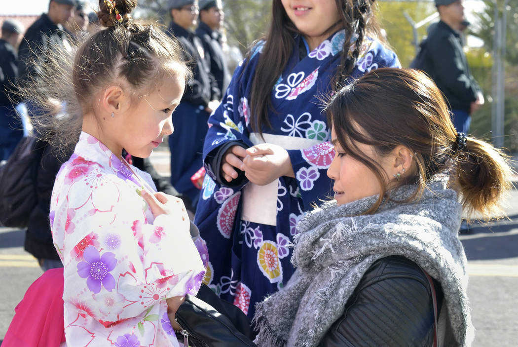 May Lantz, right, adjusts the costume of her daughter Ema (cq), 6, while waiting for a parade to begin during Chinese New Year celebrations on Fremont Street in Las Vegas on Saturday, Feb. 9, 2019 ...