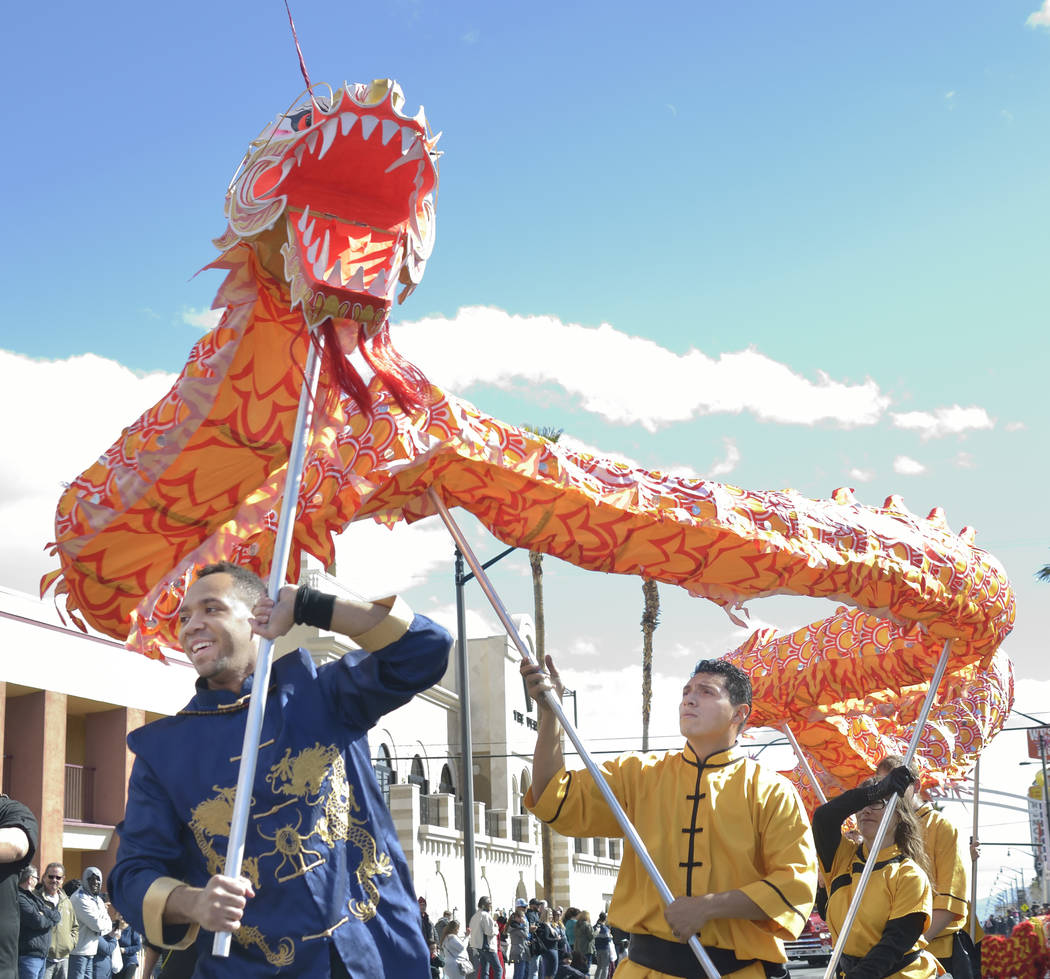 Keith Hasson, left, and Oscar Cisneros from the Lohan School of Shaolin Kung Fu march in a parade during Chinese New Year celebrations on Fremont Street in Las Vegas on Saturday, Feb. 9, 2019. (Bi ...