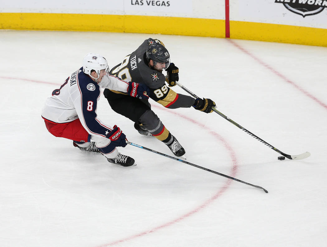 Vegas Golden Knights right wing Alex Tuch (89) reaches for the puck while being guarded by Columbus Blue Jackets defenseman Zach Werenski (8) during the second period of an NHL hockey game at T-Mo ...
