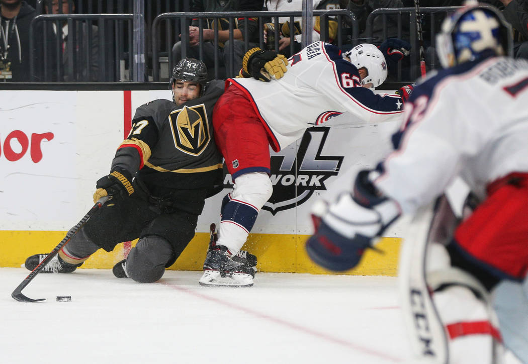 Vegas Golden Knights left wing Max Pacioretty (67) reaches for the puck while leaning on Columbus Blue Jackets defenseman Markus Nutivaara (65) during the third period of an NHL hockey game at T-M ...