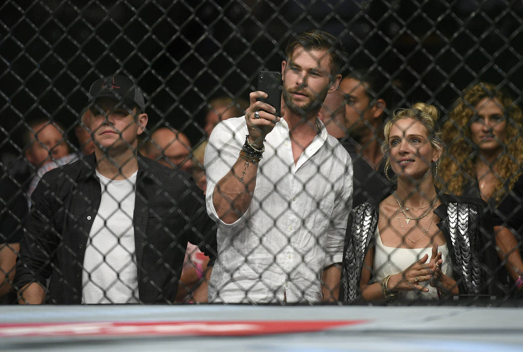 Actors, Matt Damon, left, Chris Hemsworth, center, and his wife Elsa Pataky watch Nigeria's Israel Adesanya and Brazil's Anderson Silva during their middleweight bout at the UFC 234 event in Melbo ...