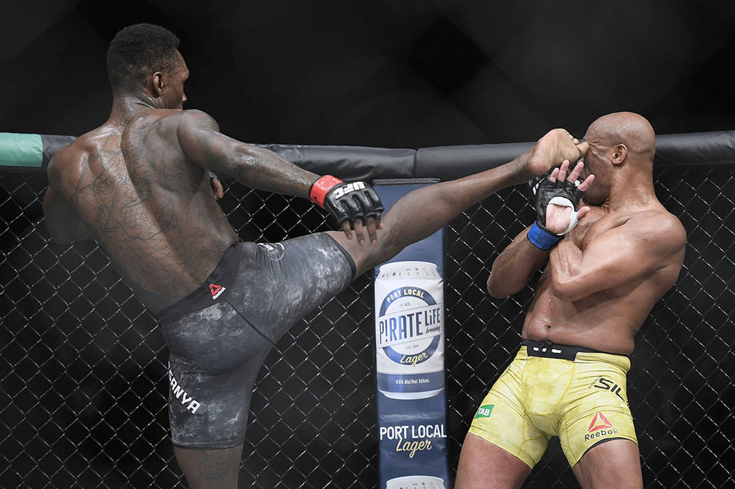Nigeria's Israel Adesanya, left, kicks Brazil's Anderson Silva during their middleweight bout at the UFC 234 event in Melbourne, Australia, Sunday, Feb. 10, 2019. (AP Photo/Andy Brownbill)