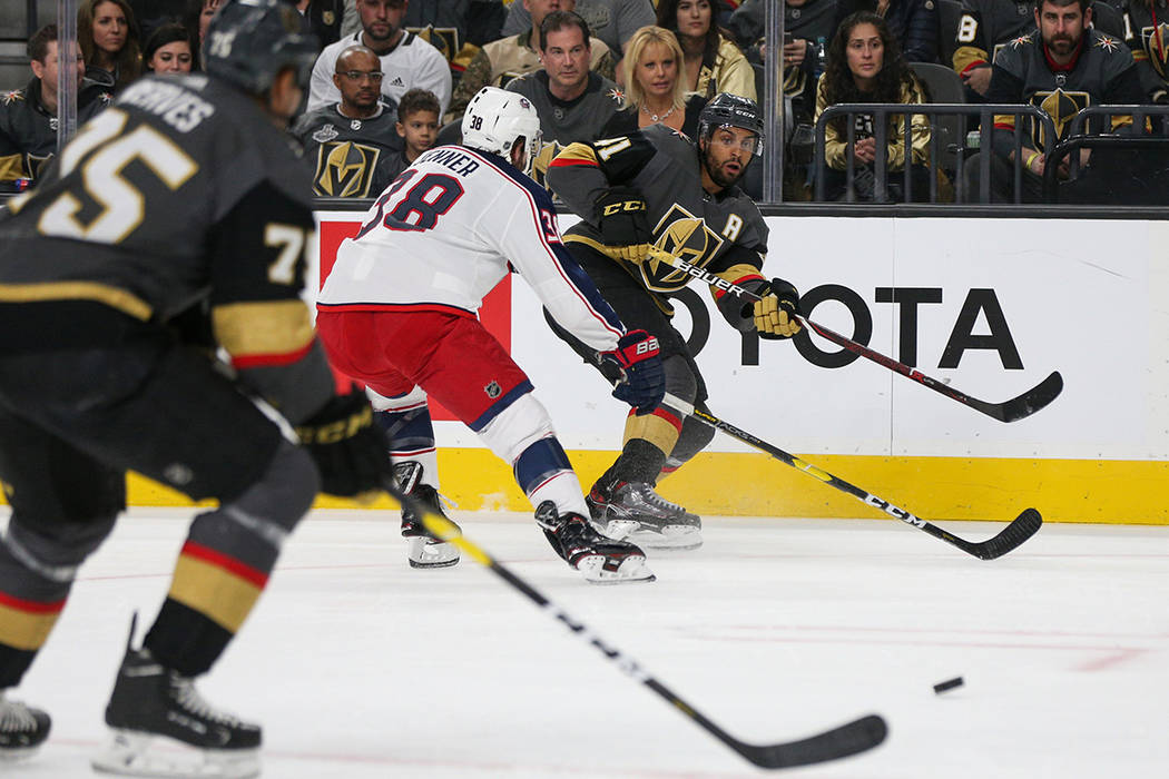 Vegas Golden Knights center Pierre-Edouard Bellemare (41) passes to Vegas Golden Knights right wing Ryan Reaves (75) while under pressure from Columbus Blue Jackets center Boone Jenner (38) during ...