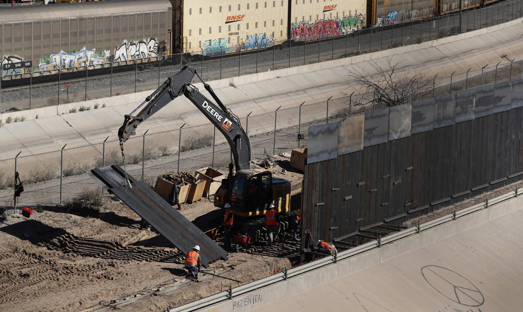 In this Tuesday, Jan. 22, 2019, photo, workers place sections of metal wall as a new barrier is built along the Texas-Mexico border near downtown El Paso. Such barriers have been a part of El Paso ...