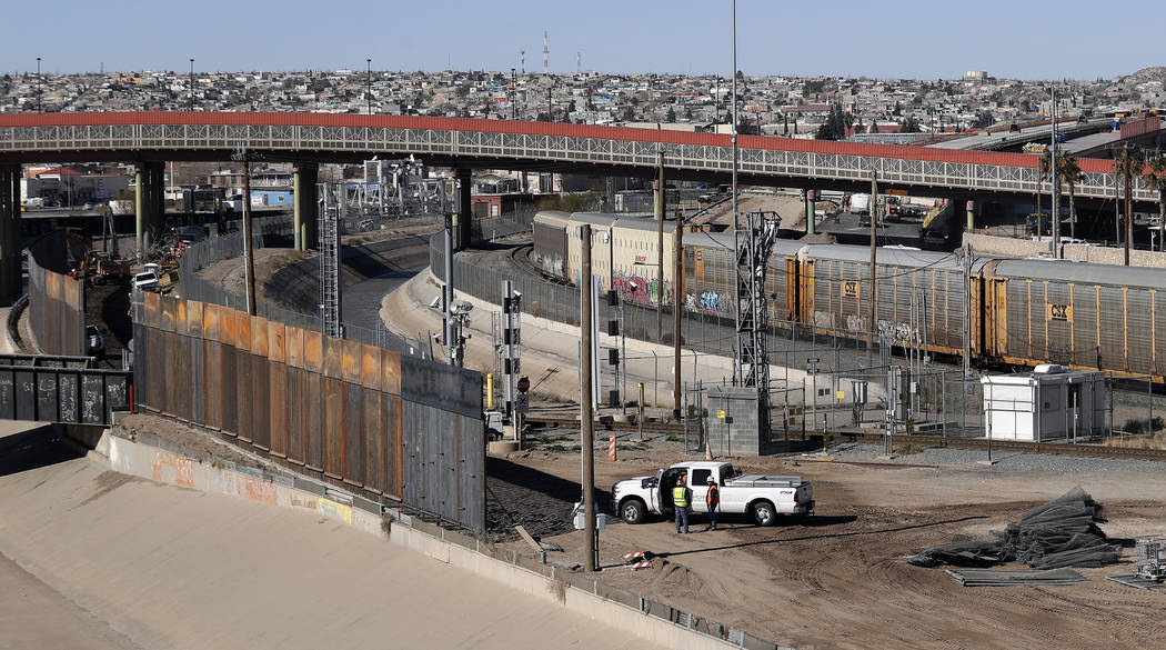 In this Tuesday, Jan. 22, 2019, photo, a new barrier is built along the Texas-Mexico border near downtown El Paso. Such barriers have been a part of El Paso for decades and are currently being exp ...
