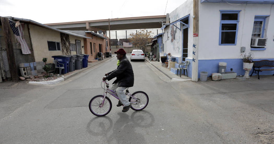 In this Monday, Jan. 21, 2019, photo, Mario Silva leaves his home on a bike in El Paso, Texas. Silva's home backs up to a border barrier that runs along the Texas-Mexico border in El Paso.n(AP Pho ...