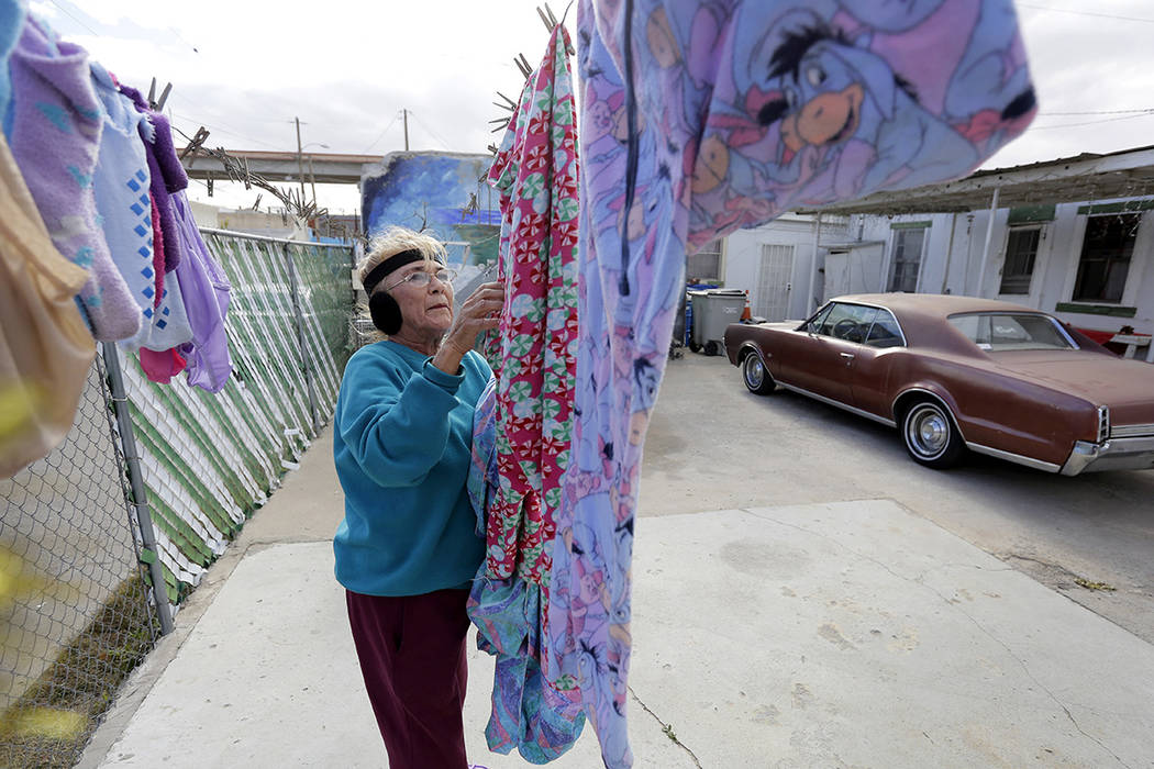 In this Tuesday, Jan. 22, 2019, photo, Mickie Subia gathers her laundry at her home in El Paso, Texas. Subia lives less than a block away from a border barrier that runs along the Texas-Mexico bor ...
