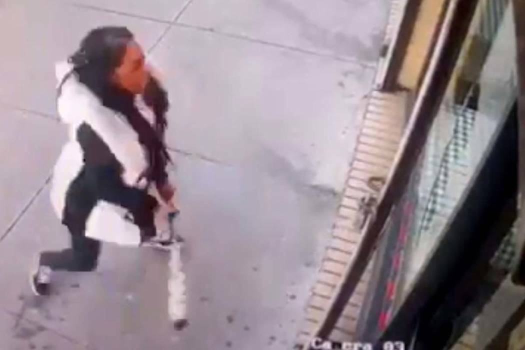 "In this Jan. 15, 2019 image taken from surveillance video, a woman smashes the windows of ""Back Home Restaurant"" in the Bronx borough of New York. Police say that she became upset after ordering a ..."