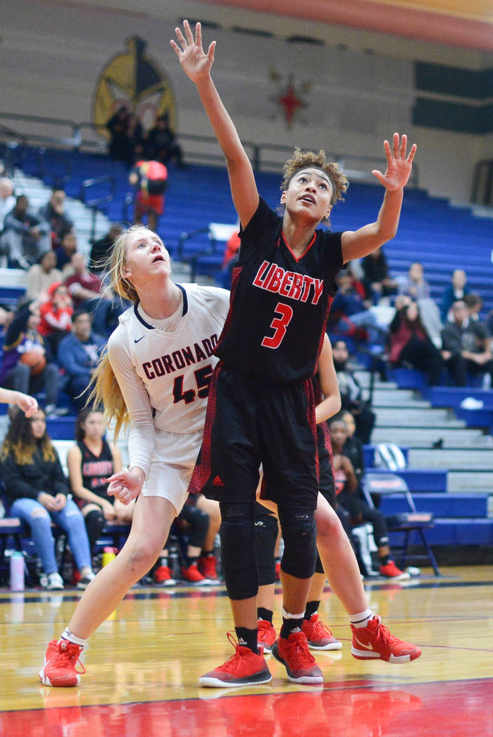 Liberty senior Journie Augmon (3) battles for position with Coronado senior Haley Morton (45) while waiting for a rebound in the second quarter of a game between Coronado High School and Liberty H ...