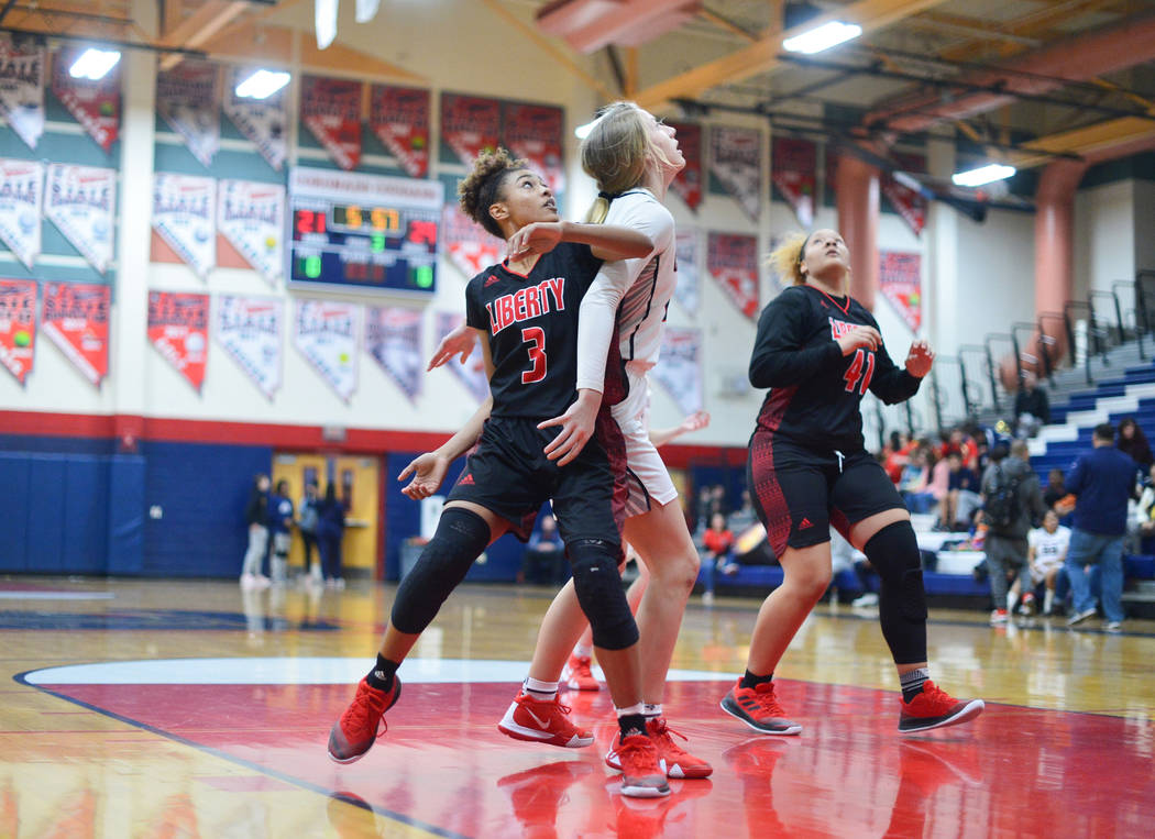 Liberty senior Journie Augmon (3) battles for position with Coronado senior Haley Morton (45) while waiting for a rebound in the third quarter of a game between Coronado High School and Liberty Hi ...