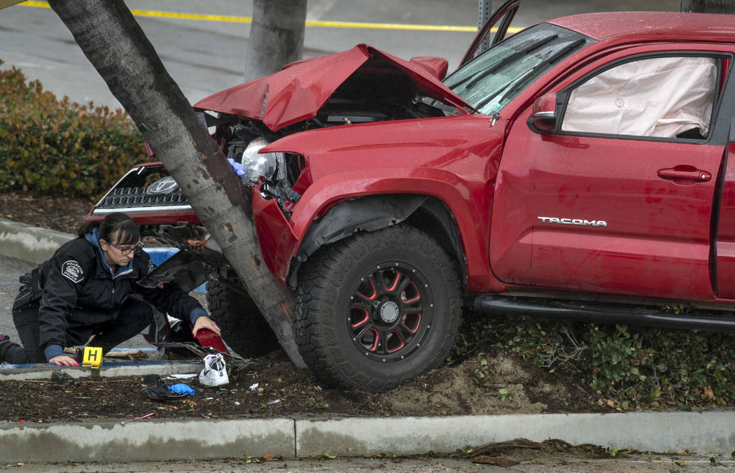 Heather Barclay, bottom left, an accident investigator with the Fullerton Police Department, gathers evidence from an early-morning accident involving a suspected DUI driver on Sunday, Feb. 10, 20 ...