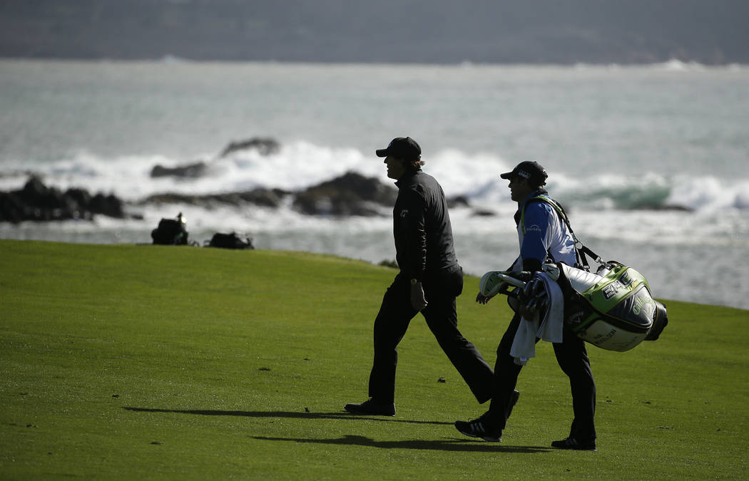 Phil Mickelson, left, walks with his brother and caddie Tim Mickelson up the fourth fairway of the Pebble Beach Golf Links during the final round of the AT&T Pebble Beach Pro-Am golf tournamen ...