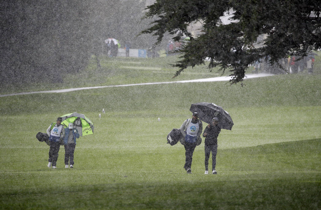 Si Woo Kim, left, of South Korea, and Scott Langley, right, walk in a hailstorm up the second fairway of the Pebble Beach Golf Links during the final round of the AT&T Pebble Beach Pro-Am golf ...