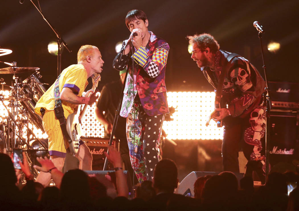 Flea, from left, and Anthony Kiedis, of Red Hot Chili Peppers, and Post Malone perform a medley at the 61st annual Grammy Awards on Sunday, Feb. 10, 2019, in Los Angeles. (Photo by Matt Sayles/Inv ...