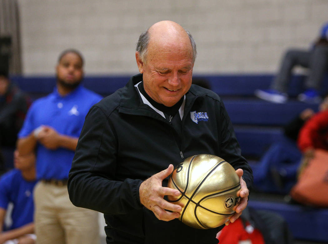 Basketball official Neil Gallant holds a golden basketball that he was presented with, honoring his time as a referee during a game at Democracy Prep at Agassi Academy Campus in Las Vegas, Monday, ...