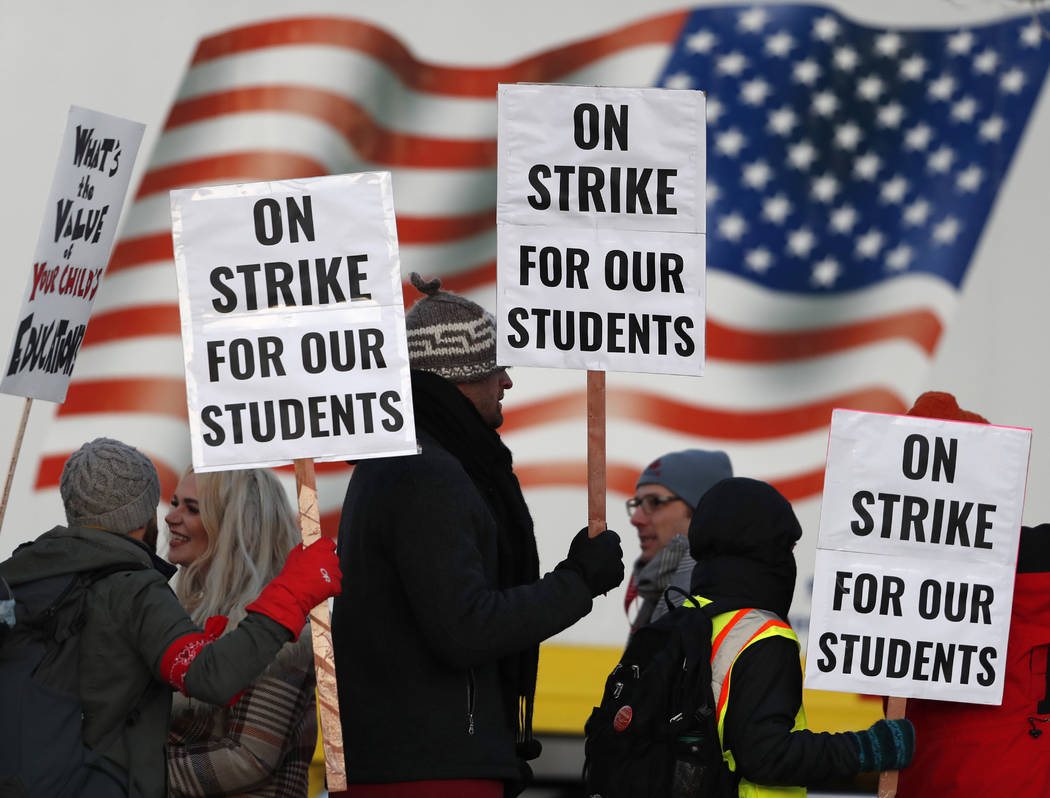 Teachers carry placards as they walk a picket line outside South High School early Monday, Feb. 11, 2019, in Denver. The strike on Monday is the first for teachers in Colorado in 25 years after fa ...