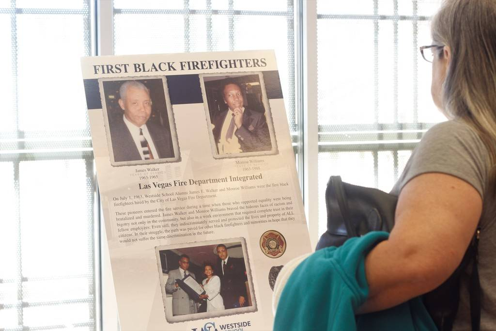 An attendee of the event observes a part of the History of Black Firefighters photo exhibit at the Doolittle Senior Center on a recent Saturday. (Mia Sims/Las Vegas Review-Journal @miasims___)